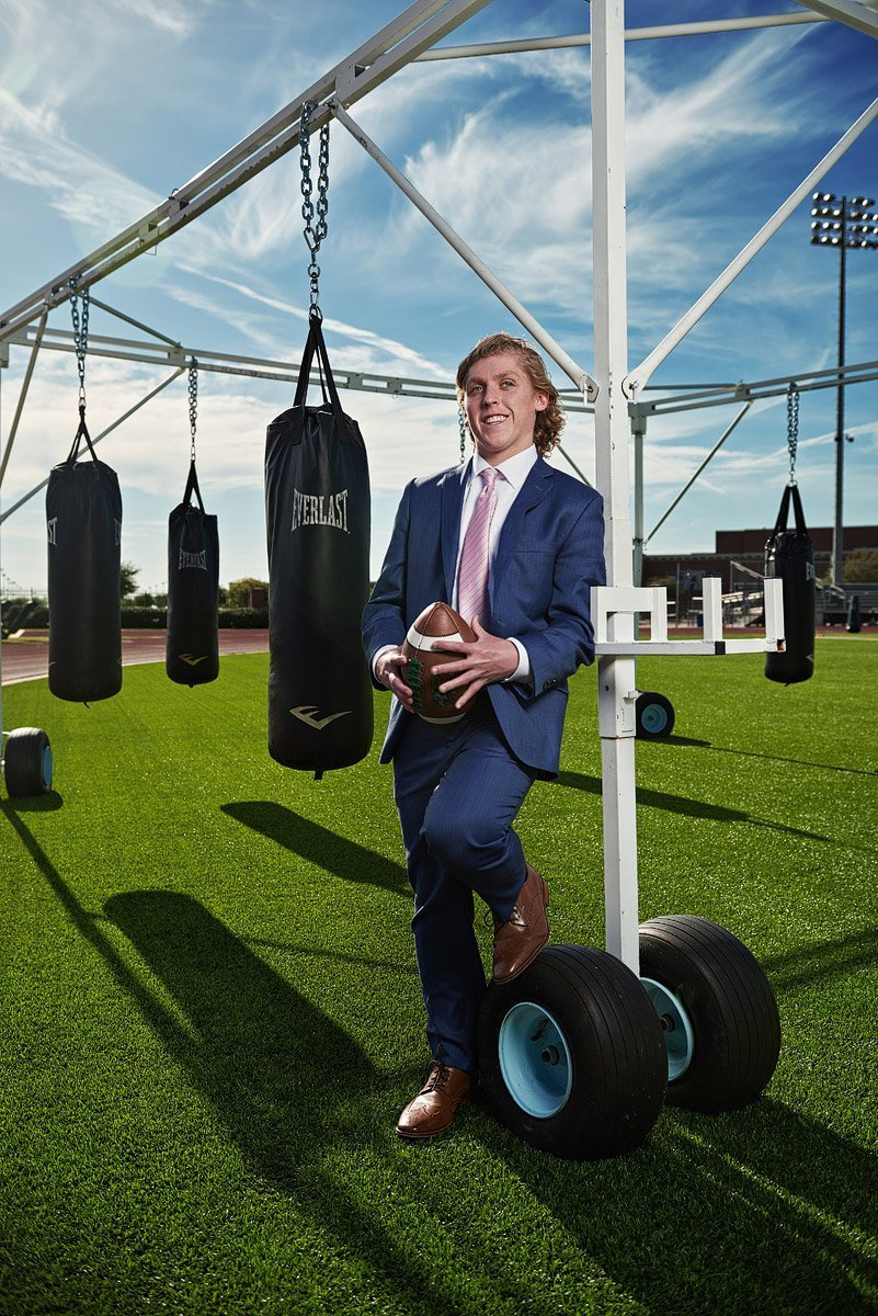 prosper senior pictures football player by punching bags on the practice field