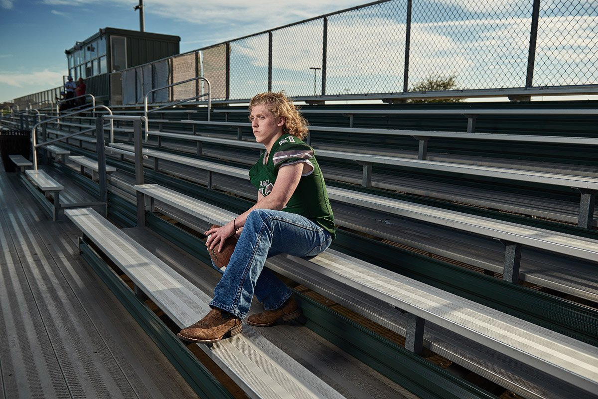 prosper senior pictures of football player in green jersey holding a football in the bleachers