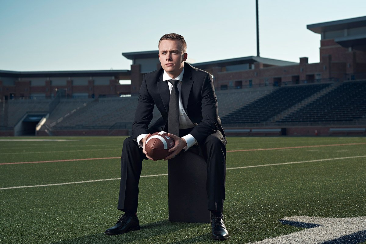 Allen senior sports portraits in a suit on the field at eagles stadium