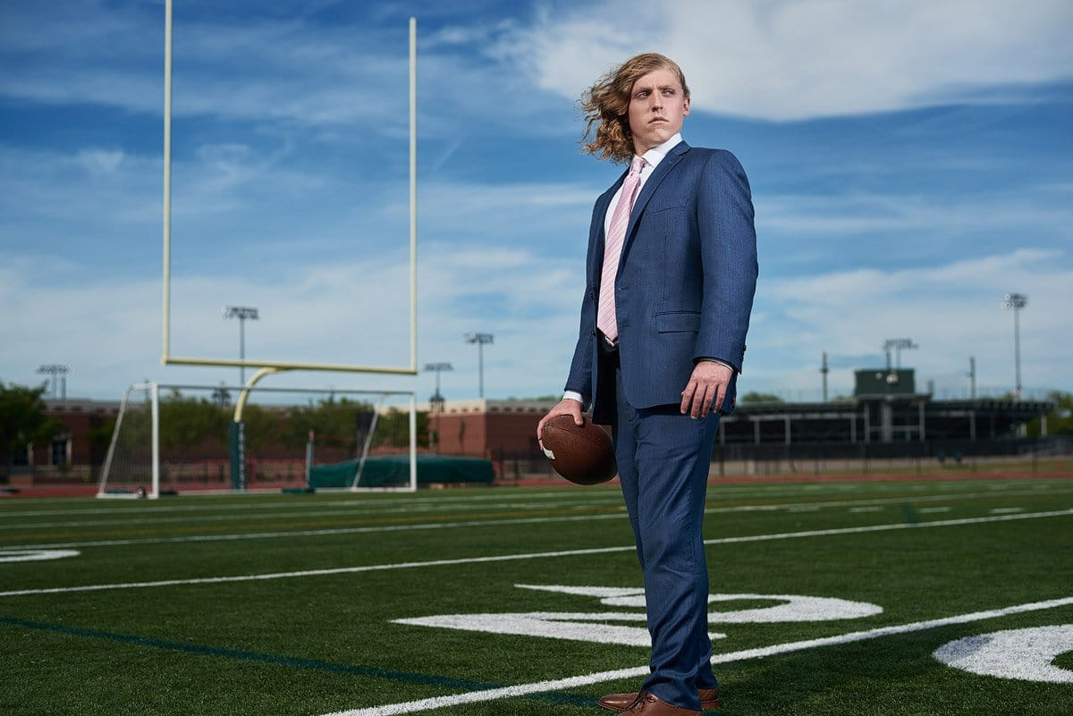 prosper senior pictures high school football practice field in blue suit