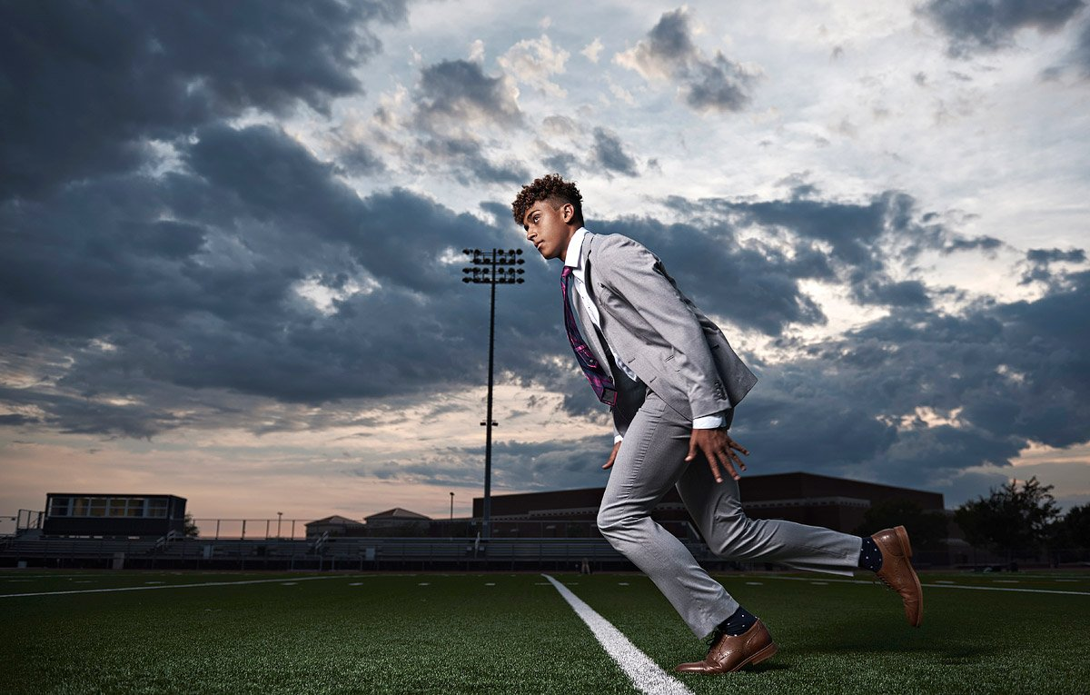 Senior Pictures in McKinney of football receiver running across field in suit