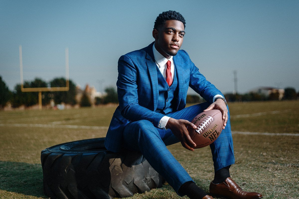 McKinney North Senior Portraits football player sits on tire in blue suit