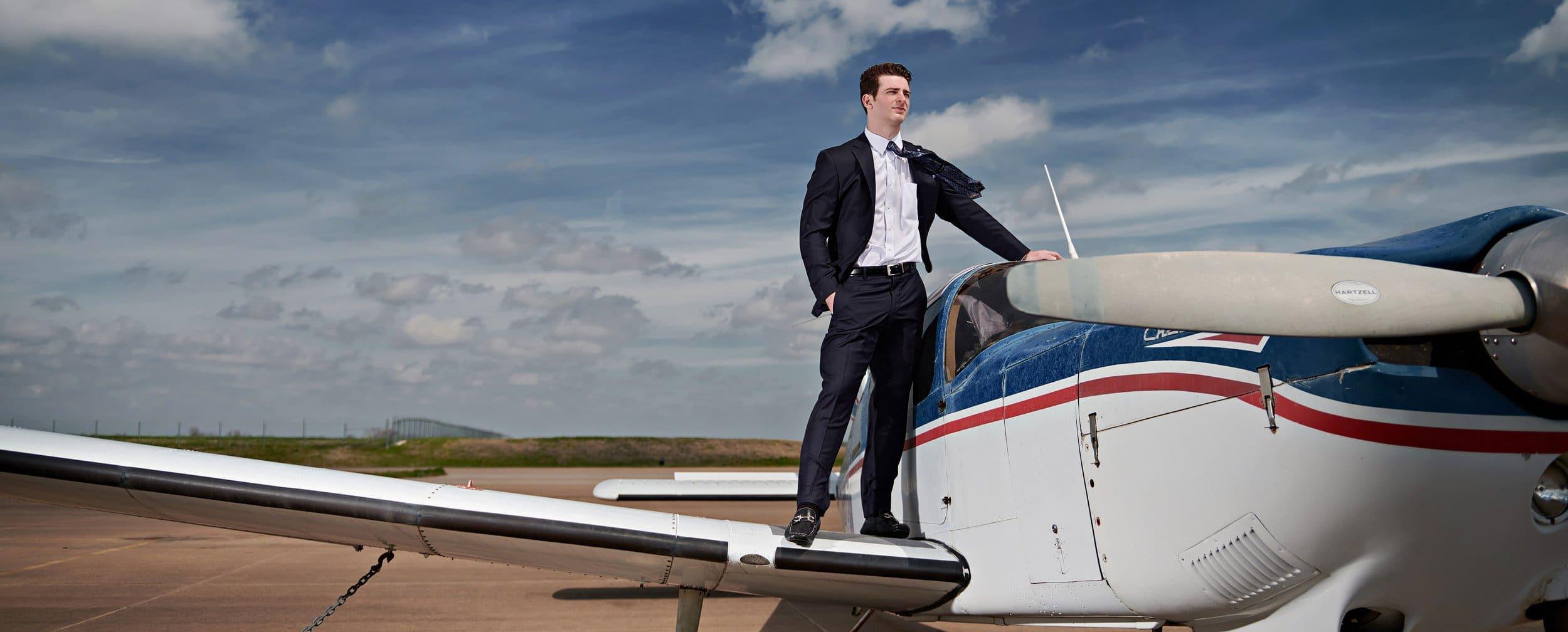 prosper senior photographer student on plane wing for portraits in suit banner