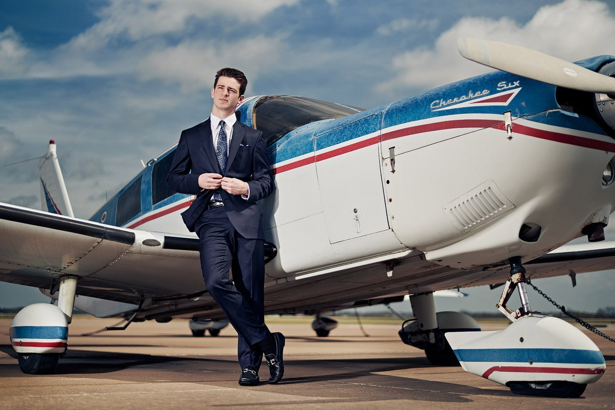 prosper senior photographer with plane of student at the airport in suit