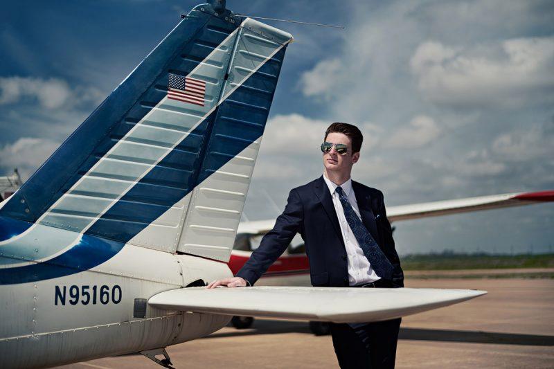 prosper senior photographer photographs student by plane with sunglasses