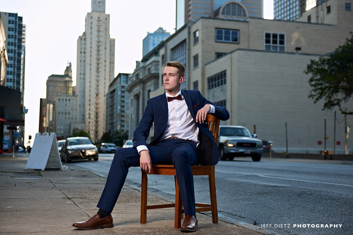 frisco liberty senior pictures in downtown dallas in a chair with suit
