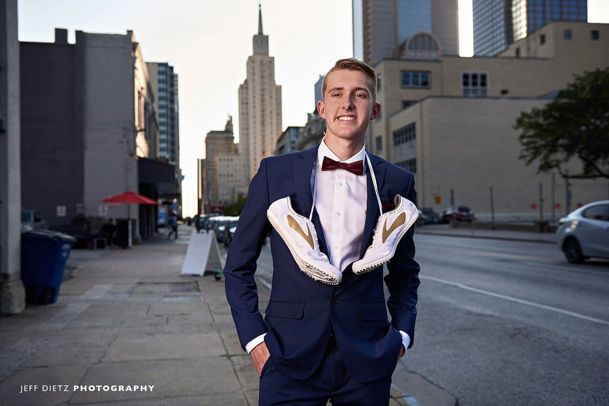 frisco liberty senior track poses for photos with cleats around neck in downtown dallas