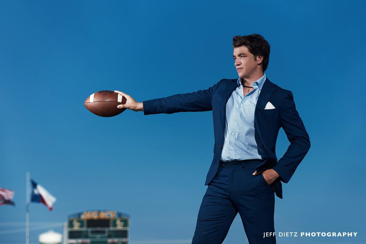legacy Christian Senior Football player in a suit holding the football