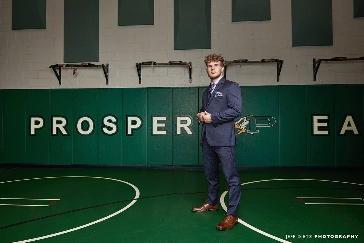 prosper wrestling room with senior rylan in a suit for senior portraits