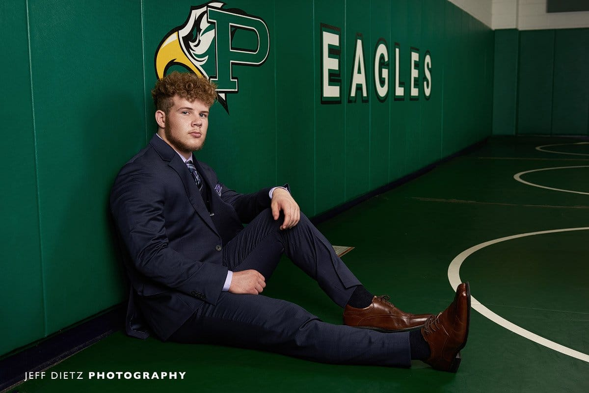 prosper senior wrestler leaning up against the wall in the practice gym for portraits