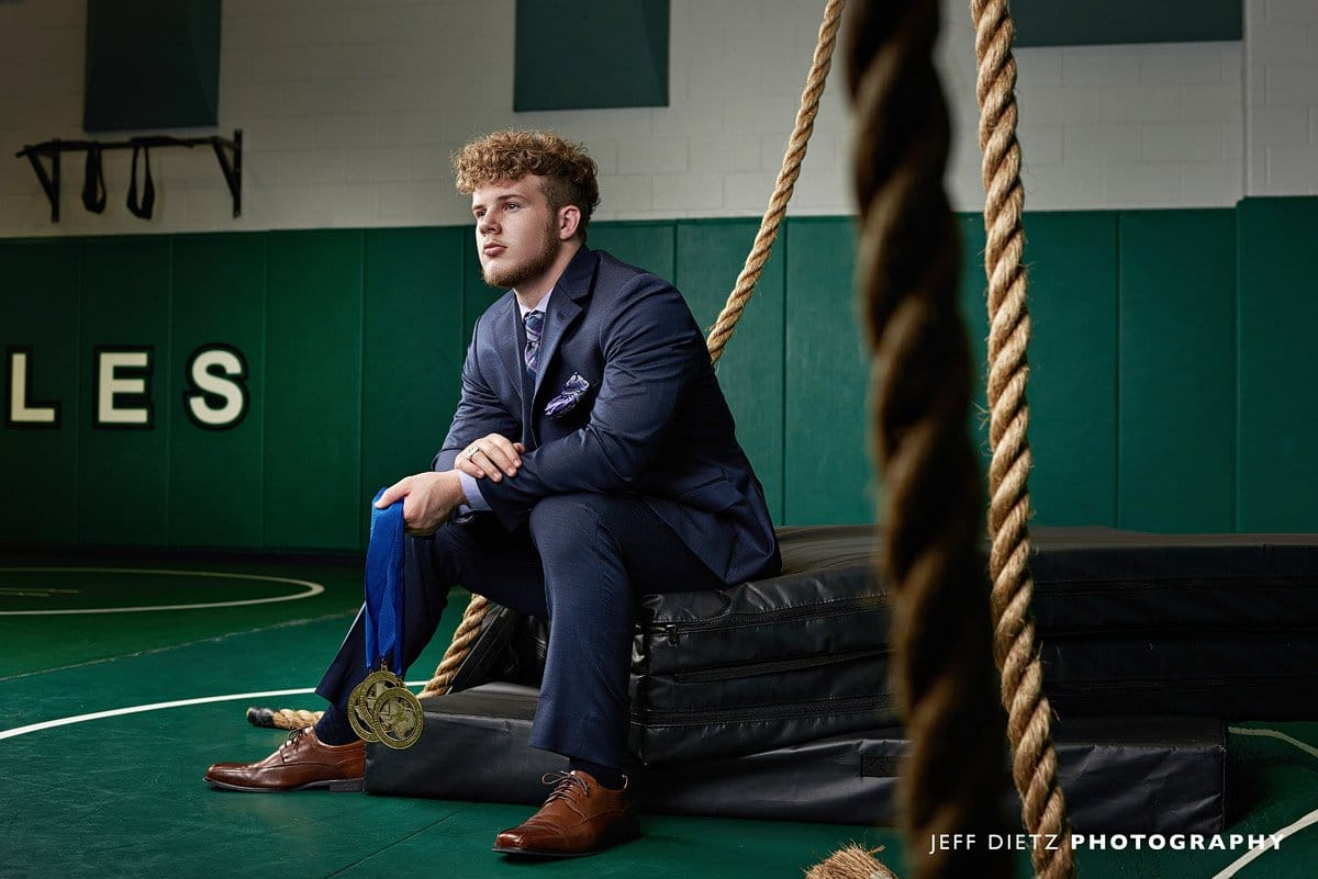 Prosper Wrestling senior portraits at the high school gym with ropes and suit