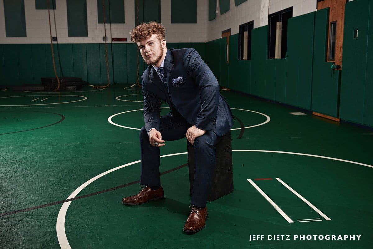 prosper wrestler sitting on the mats in the practice gym for senior portraits