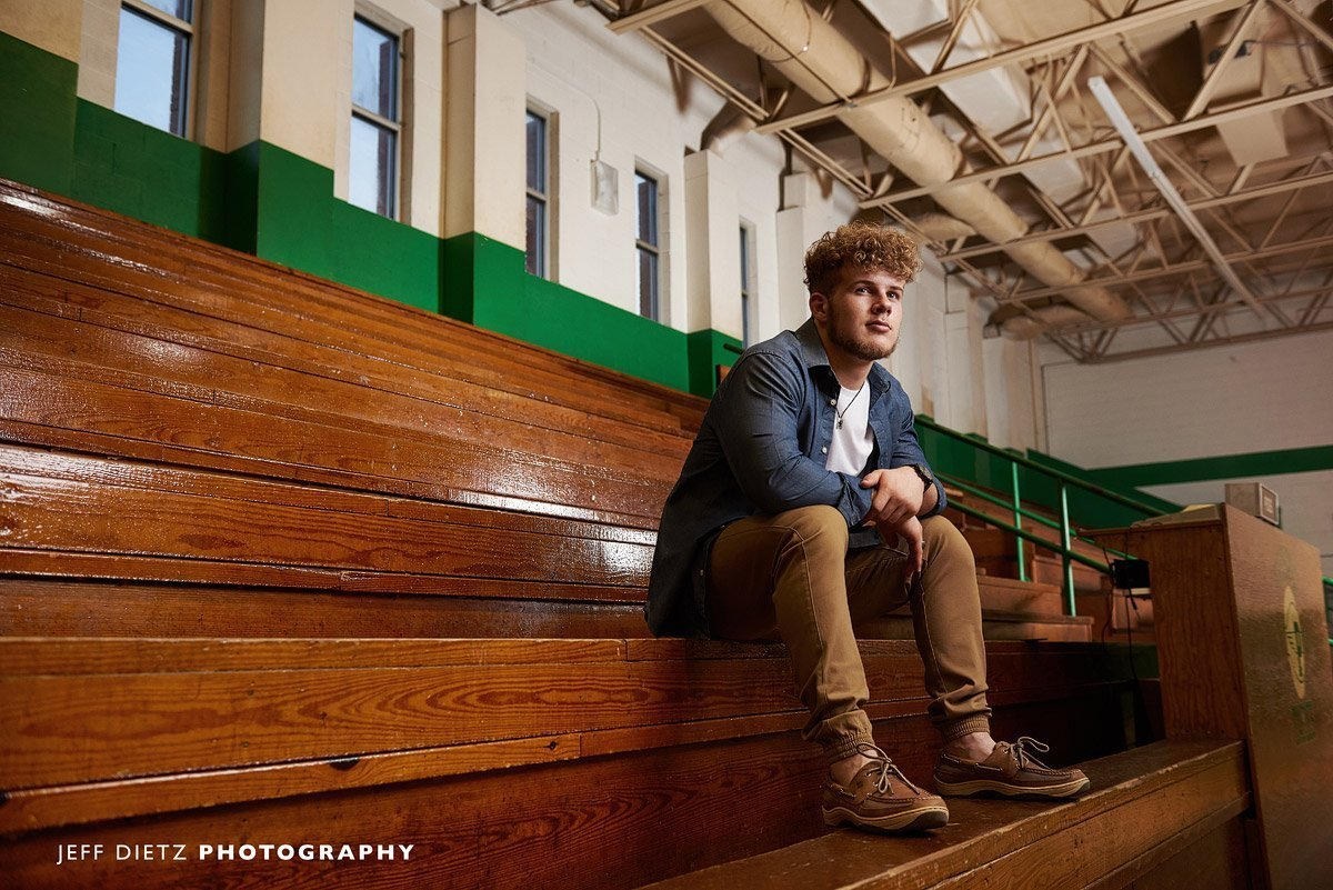 prosper senior guy sitting on the bleachers in the gym for senior pictures
