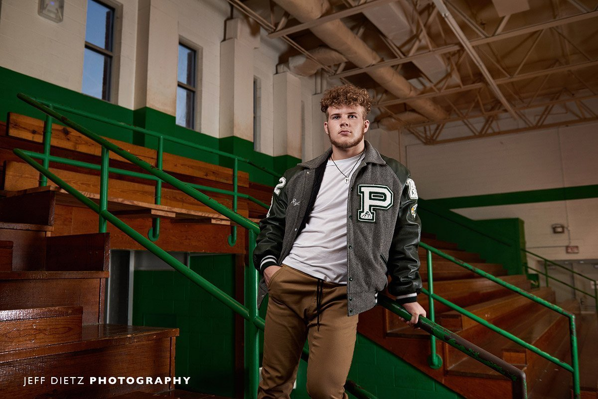 senior prosper wrestler in letterman jacket in old wood gym