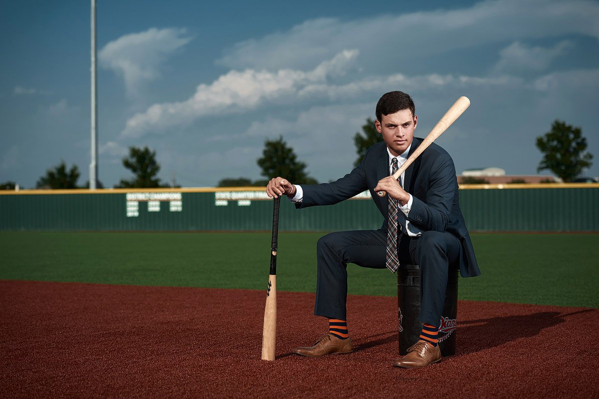 Mckinney north senior baseball player holding two bats on the mnhs field in mckinney texas