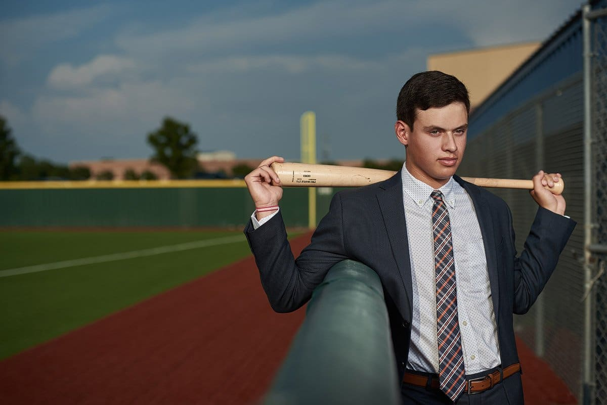 mckinney north senior baseball player poses with his bat behind his shoulders for his senior pictures