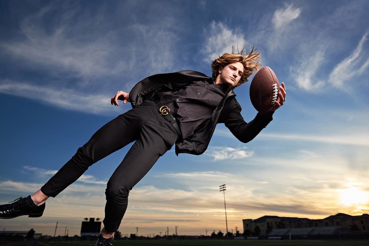 Prestonwood Senior Portraits of Riley diving for football in suit christian academy plano tx