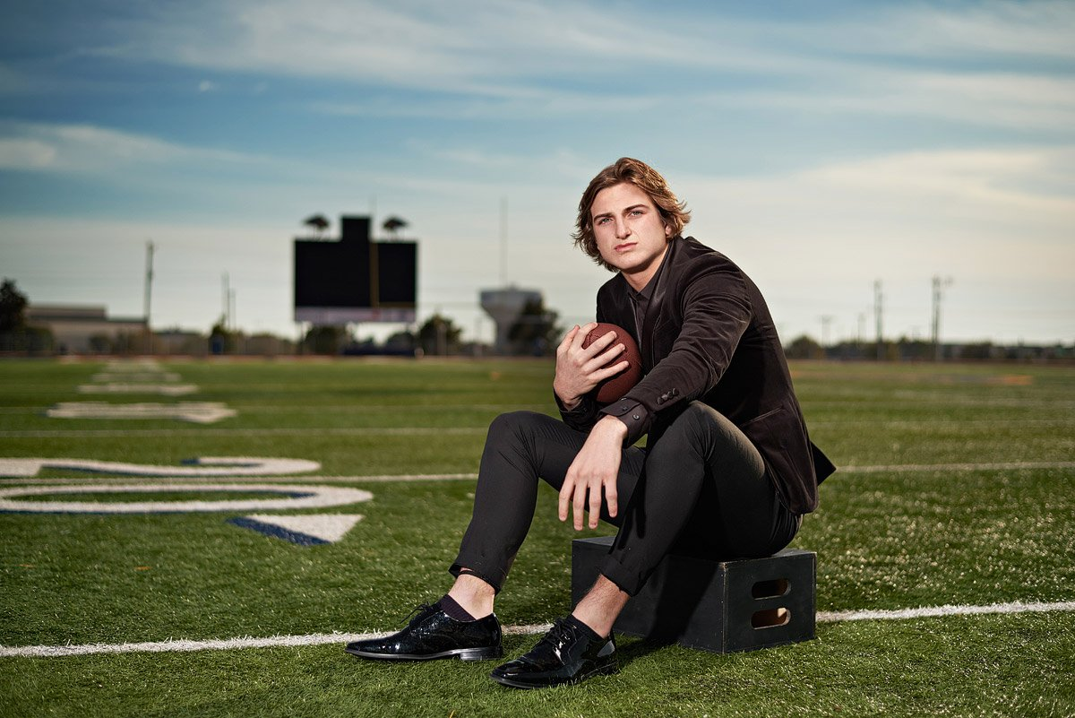 Prestonwood Christian senior portraits on the field with wide receiver in black suit