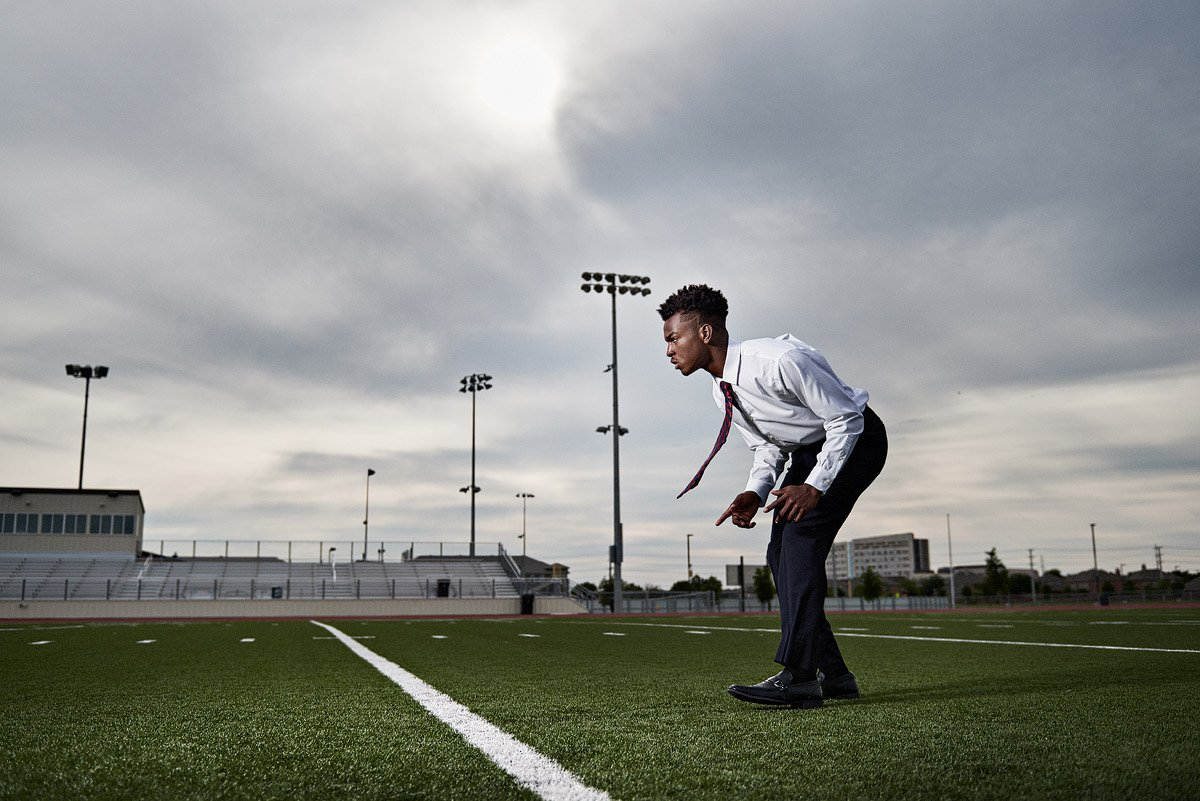 frisco senior portraits of wide receiver in a tie on the football field
