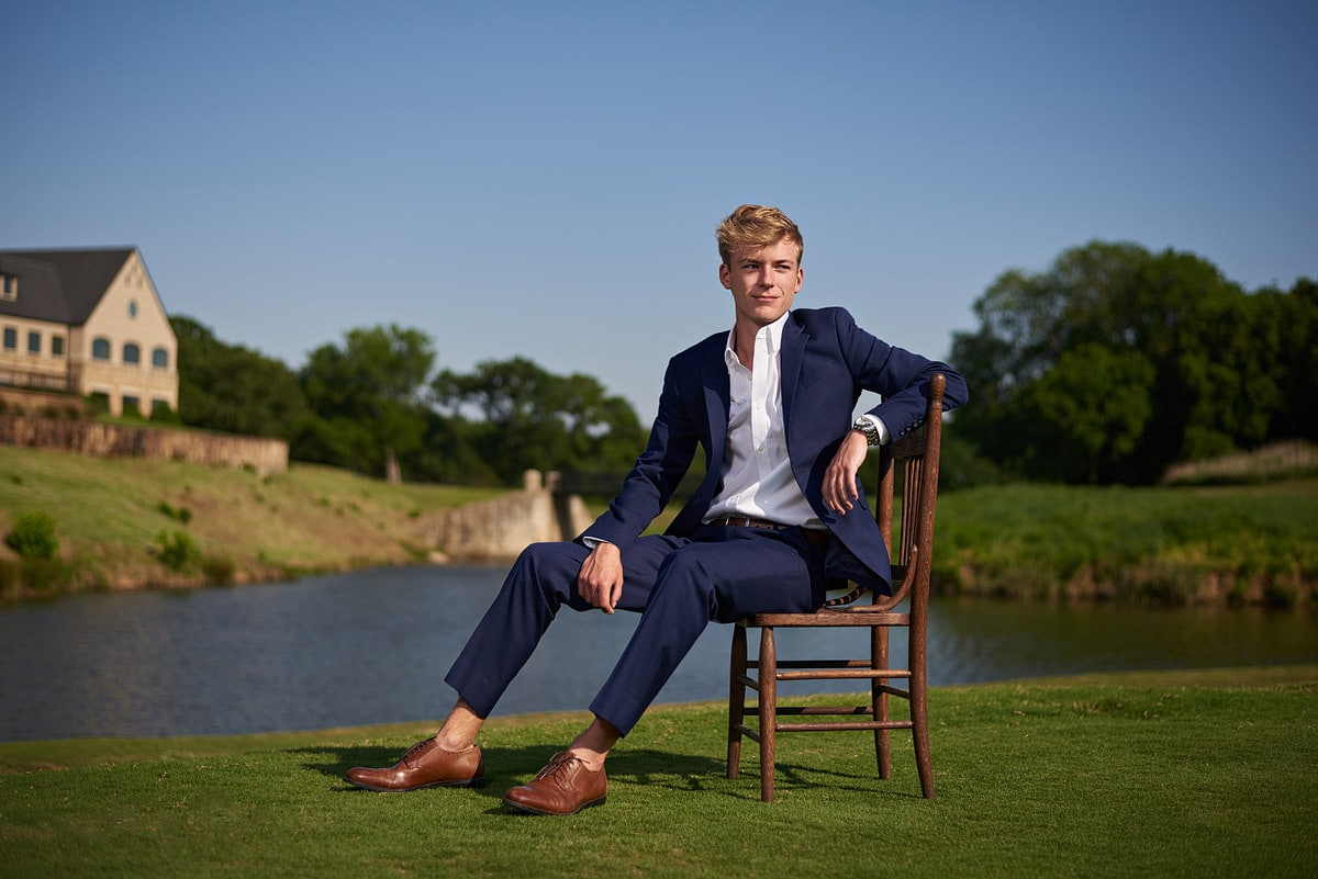 southlake senior sits in wooden chair on the golf course in a suit