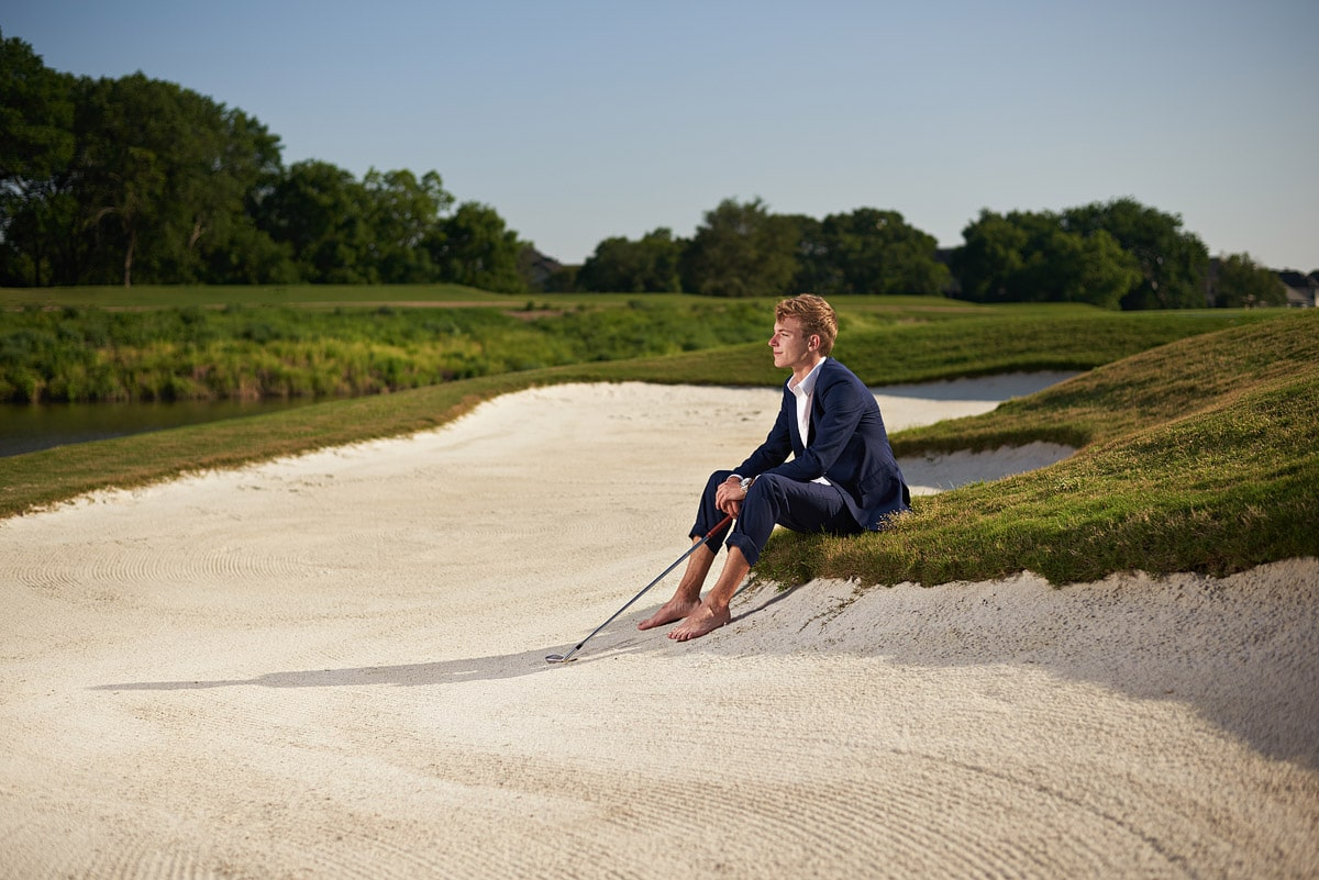 senior sitting in the sand trap at southlake country club
