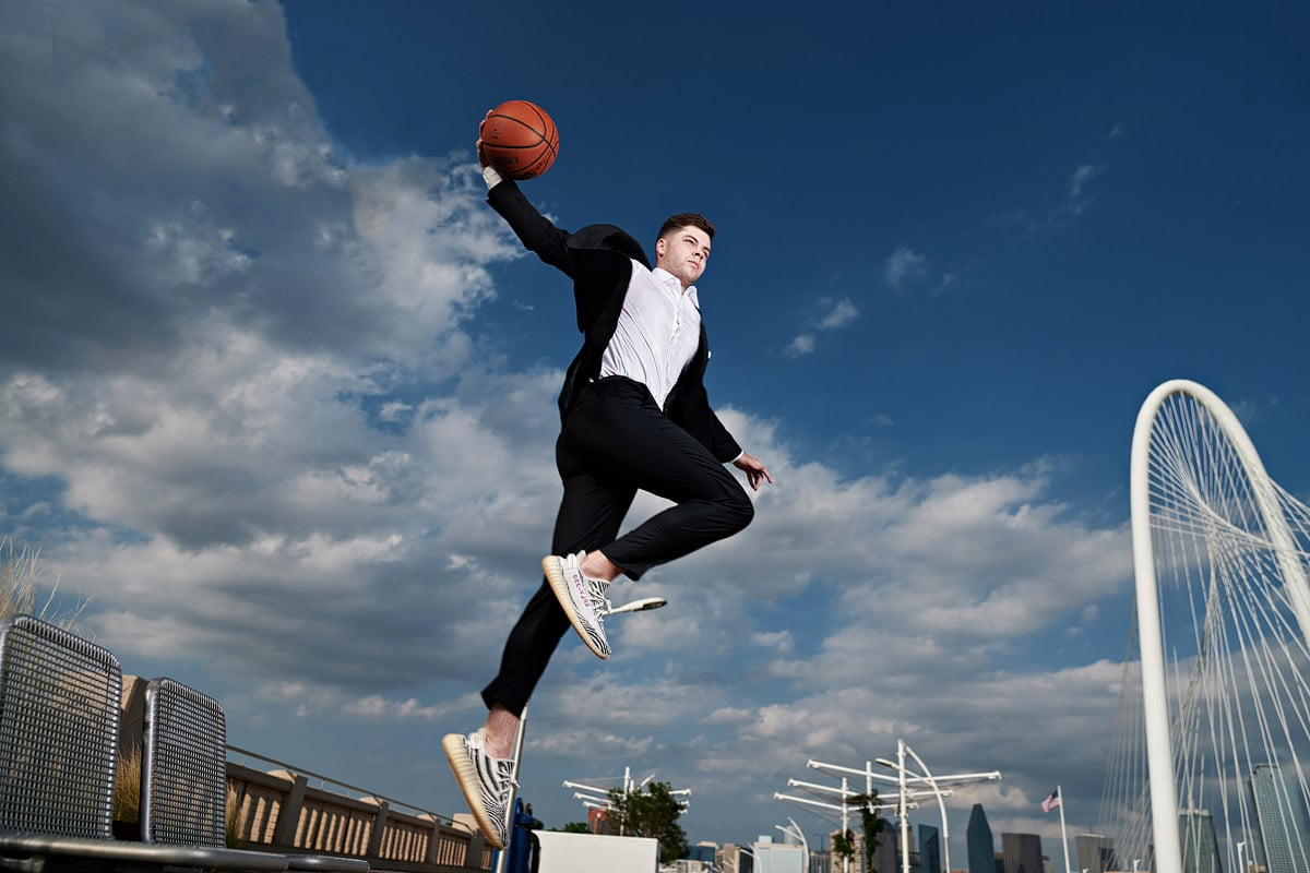 Bishop Lynch Senior Portraits of basketball player dunking and flying in the air on dallas bridge
